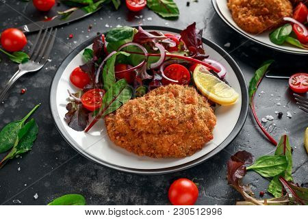 Breaded Chicken Kiev Breast Stuffed With Butter, Garlic And Herbs Served With Vegetables In A Plate