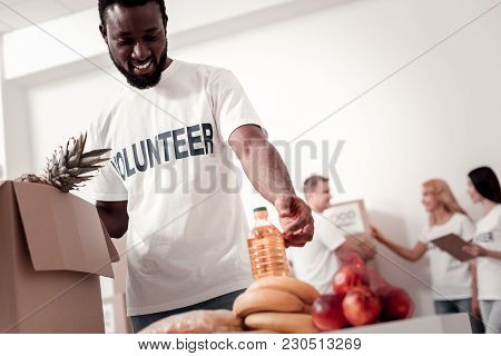 Work With Pleasure. Young Male Person Bowing Head And Expressing Positivity While Looking At Bottle