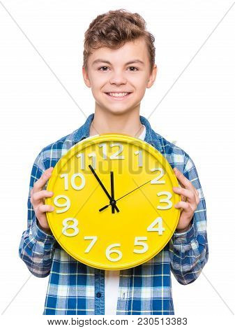 Portrait Of Caucasian Teen Boy With Clock. Funny Teenager Showing Yellow Clock, Looking At Camera. C