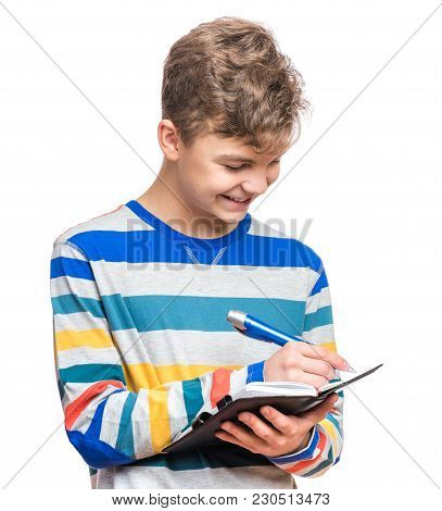 Portrait Of Caucasian Smiling Teen Boy With Notebook And Blue Pen Writing Something. Handsome Funny