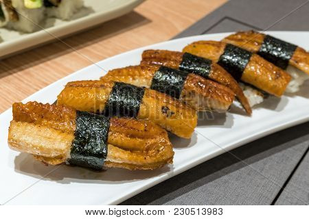 Unagi Eel Sushi Wrapped Over Rice With Seaweed On White Ceramic Plate Closeup Macro