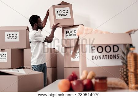 Humanitarian Help. Concentrated Brunette Holding Box And Raising Hands While Standing In Semi Positi