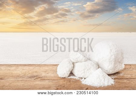 Salt On Table. Lumps Of Salt With Salty Lake In The Background. Salt Produced On Farm