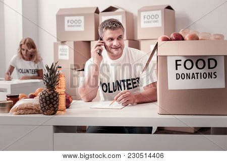 Food Donations. Positive Delighted Volunteer Keeping Smile On His Face And Turning Head While Talkin