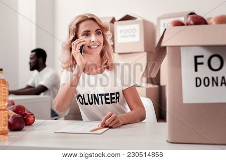 Listening You. Attractive Blonde Expressing Positivity And Looking At Big Box While Talking Per Tele