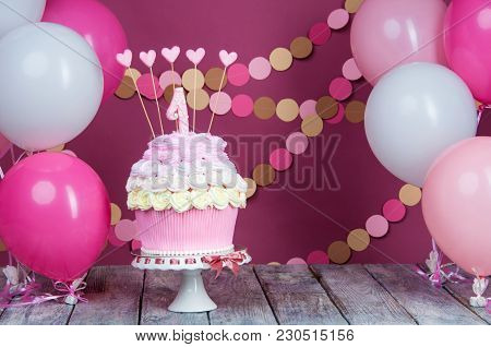 First Birthday Cake With A Unit On A Pink Background With Balls And Paper Garland