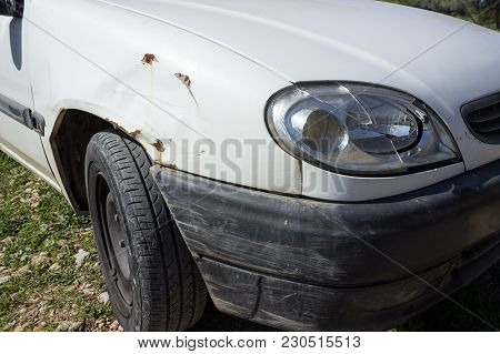 White Car With A Broken Headlight And Front Wing. Concept - Accident, Car Insurance, Damage Assessme