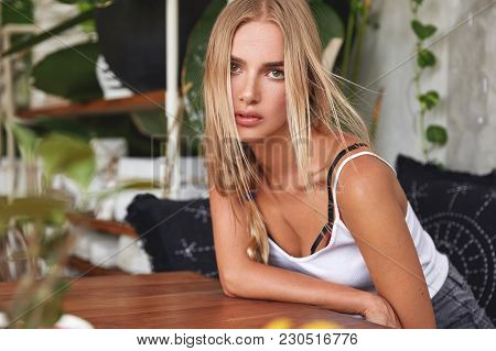 Portrait Of Serious Beautiful Female Model With Luxurious Blonde Hair Sits At Table On Sofa, Waits F