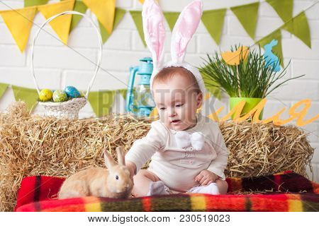 Cute Little Baby Wearing Bunny Ears On Easter Day And Touching Rabbit