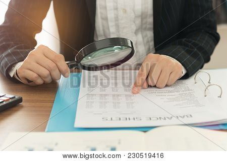 Business Women Using Magnifying To Review Balance Sheet Annual. Concept Of Internal Audit, Auditing