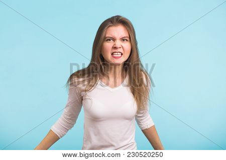Angry Aggressive Woman With Ferocious Expression On Blue Background.