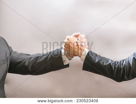 Two Businessmen Partner To Greet Each Other, A Firm Handshake.