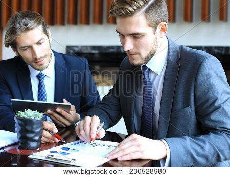 Two Young Businessmen Analyzing Financial Document At Meeting