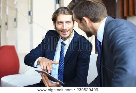 Two Young Businessmen Using Touchpad At Meeting