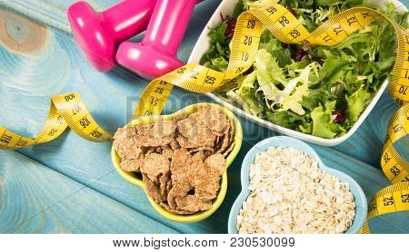 Healthy Eating, Dieting, Slimming And Weigh Loss Concept -dumbeells, Measuring Tape And Salad.