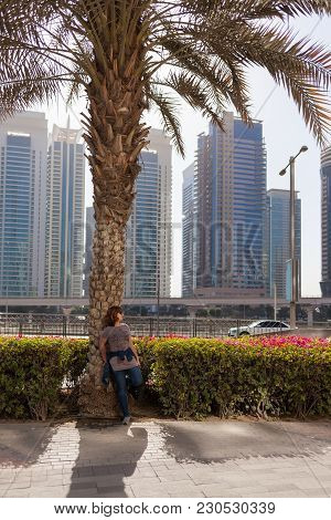 Woman Leaned On Palm Tree With Dubai Skyline In Backgound At Beautiful Sunny Morning.