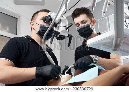 Male Dentist Looks In A Microscope Curing Patient's Teeth, Another Male Doctor Assists Him