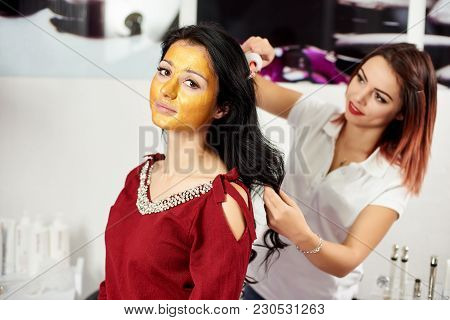 Woman Uses Darsonval For Massage Head's Skin, With Gold Mask On Face In A Beauty Salon.