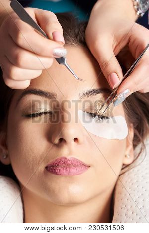 Eyelash Extension Procedure. Close-up Of The Hands Of A Beautician With Tweezers In The Hands In The