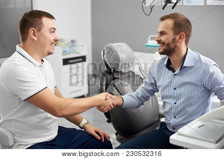 A Young Dentist And His Attractive Male Client Are Shaking Hands And Smiling In A Dental Office, Bot