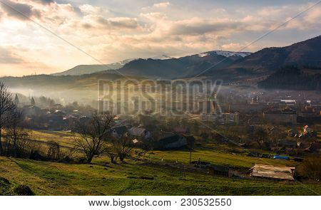 Cloudy And Foggy Sunrise In Carpathian Mountains. Small Town Volovets In The Valley At The Foot Of B
