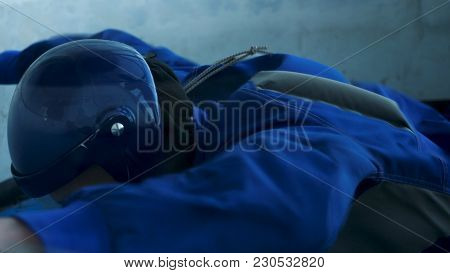 Professional Skydiver Flies In Wind Tunnel. Flying In A Wind Tunnel. Male Paratrooper Trains In Wind