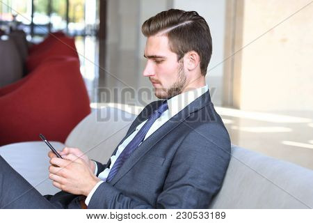 Young Businessman Sitting Relaxed On Sofa At Hotel Lobby Making A Phone Call, Waiting For Someone