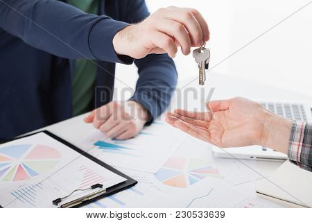 Young Business Man Giving House With Keys Of Customer At Agency Office