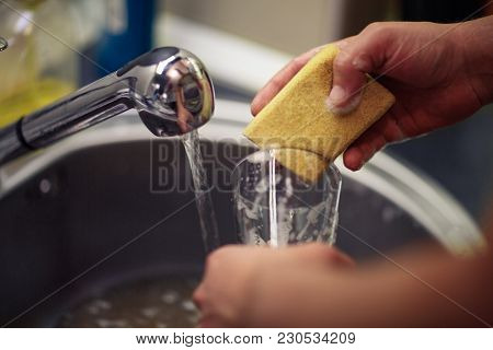 Close Up Washing Dishes. Male Hands In Foam Washes The Frying Pan With A Detergent And Sponge In The