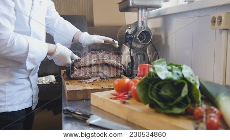 Cutting Of A Large Piece Of Smoked Meat On A Wooden Board, Concept Of Cooking And Haute Cuisine