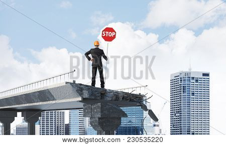 Rear View Of Engineer In Helmet Holding Stop Sign While Standing On Broken Bridge With Cityscape On