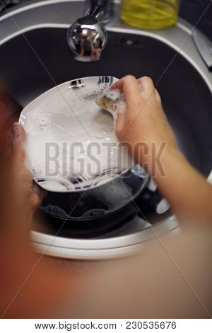 Washed Dishes- Concept Of Young Woman Washing Dishes In The Kitchen