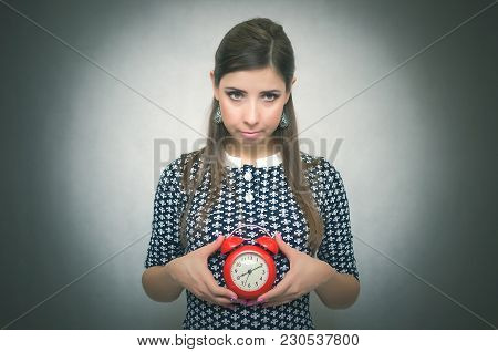 Guilty Look Woman Holding In Hands Alarm Clock And Hides Her Eyes By Looking Aside. Latecomer Studen