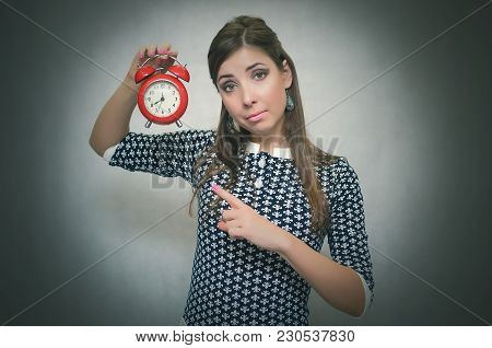 Strict Boss Woman Holding In Hands Red Alarm Clock And Showing Time By Her Index Finger. Job Or Scho
