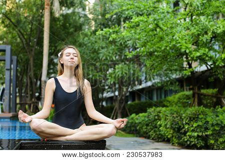 Fitness Woman Close Eyes Sitting In Lotus Position Doing Yoga By Swimming Pool On Sunny Day. Concept
