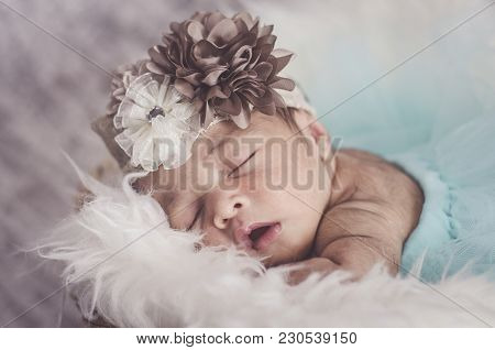 Portrait Of Cute And Adorable Newborn Baby With Head Band Sleeping In Basket Covered With Furry Mat.