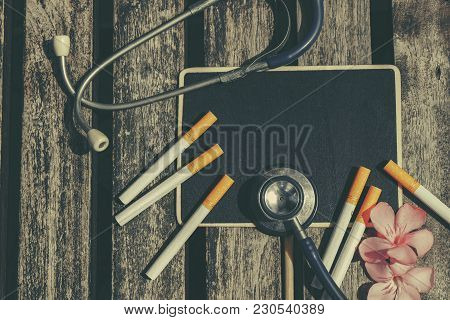 Top Lay View, Stethoscope, Cigarette, Signage And Flower On Wooden Background Ideal For Health Conce