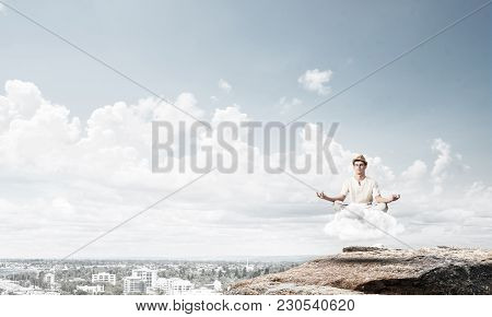 Young Man In White Clothing Keeping Eyes Closed And Looking Concentrated While Meditating On Cloud I