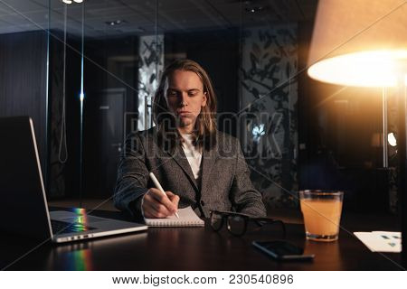 Working Process At Modern Night Office. Young Coworker Work In Coworking Studio. Businessman Uses Co