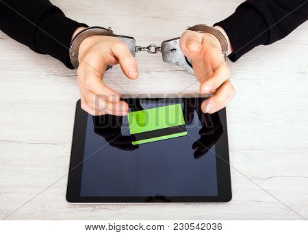 Person In Handcuffs With A Tablet And Bank Card On The Table Closeup