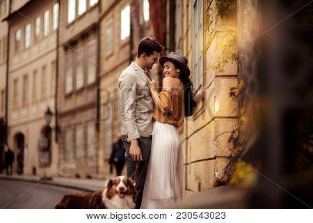 Happy Stylish Man Strolls With Dog, Embraces His Beautiful Elegant Girlfriend, Have Good Relationshi