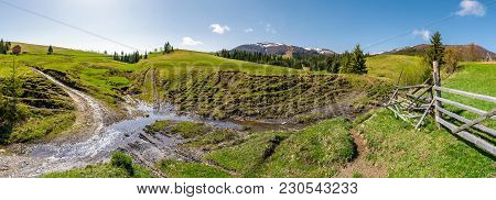 Panorama Of Mountainous Rural Countryside. Spruce Forest On Grassy Slopes. Wooden Fence Near The Bro