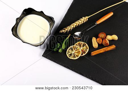 Yoghurt Plate, Mint Leaves, Slices Of Lemon, Wheat, Nuts, A Sticks Of Cinnamon And A Spoon On A Blac