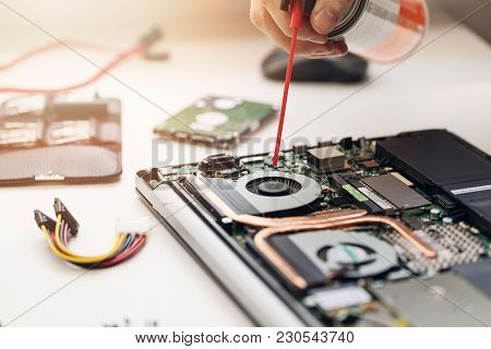 Computer Maintenance - Closeup Of Technician Blow Out Dust From Laptop Fan