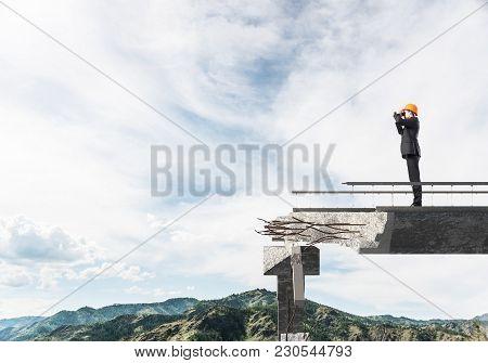 Young Engineer In Suit And Helmet Looking In Binoculars While Standing On Broken Bridge With Skyscap