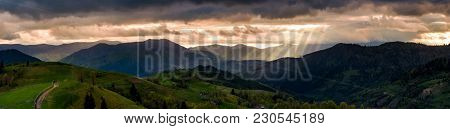 Panorama Of Mountainous Countryside At Sunset. Country Road Through Rolling Hills In To The Distance