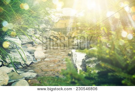 Artificial Creek With Rocks In The Summer Noon. Rays Of Sun And Bokeh.