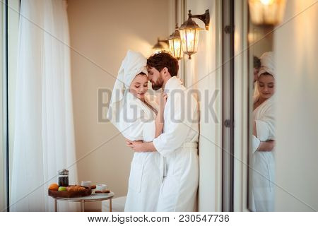 Bearded Male And His Wife Wears White Bathrobes And Towel On Head, Hug Each Other, Feel Relaxed Afte