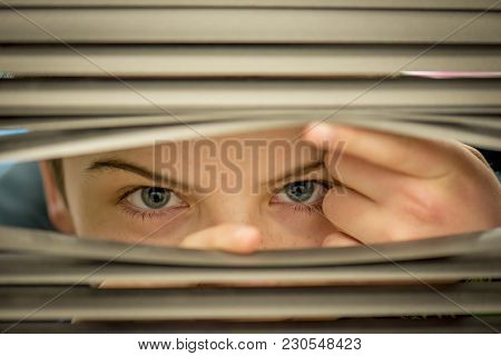 Boy Secretly Peeping Through The Blinds In Front Of Window