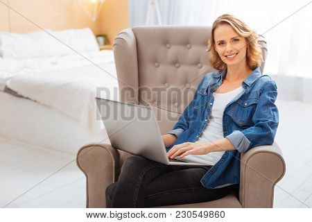 Pleasant Day. Cheerful Positive Smiling Woman Being In Her Comfortable Light Clean Bedroom And Feeli